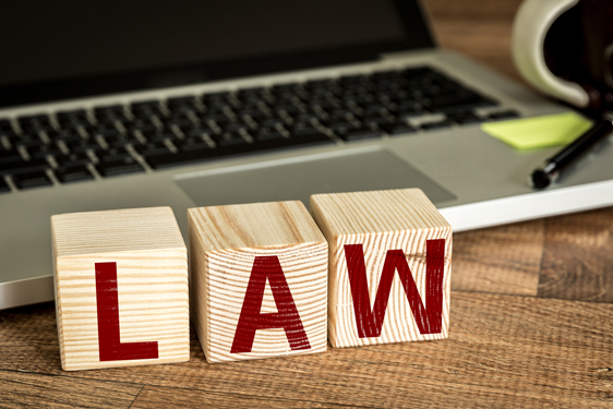 law spelled out in blocks in front of a computer