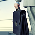 crop of man in suit holding a brief case