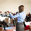 back of professionally dressed woman giving talk to meet up