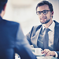 man in suit listening to another man with cup of coffee in front of him
