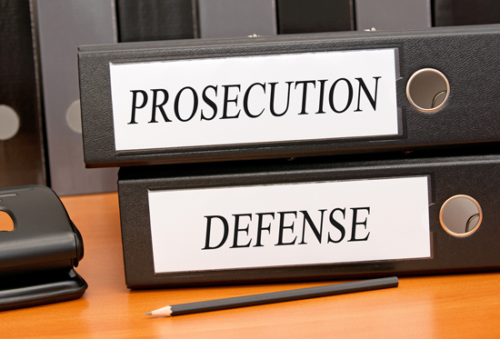 prosecution and defense binders on a desk