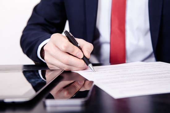 man in suits hand signing papers on a desk